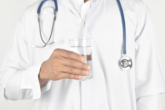 Doctor with stethoscope holding glass of water.