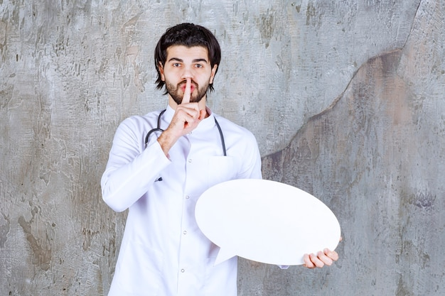 Dottore con uno stetoscopio che tiene una scheda informativa vuota ovale e chiede silenzio.