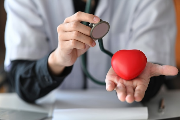 Doctor with stethoscope holding red heart in his hand. healthcare and medical concept.