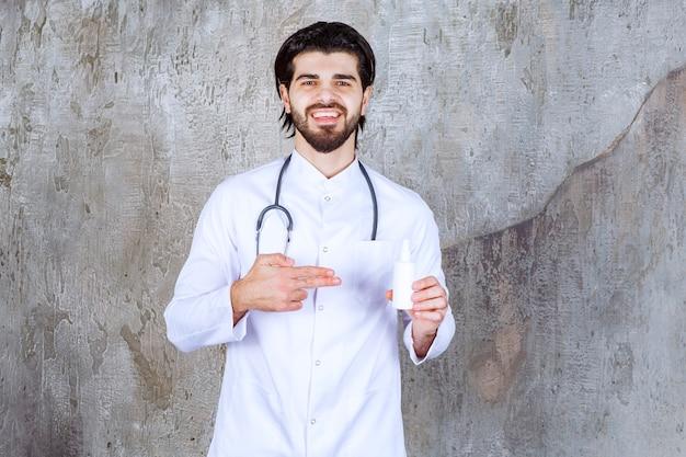 Medico con uno stetoscopio che tiene un tubo bianco di spray disinfettante per le mani