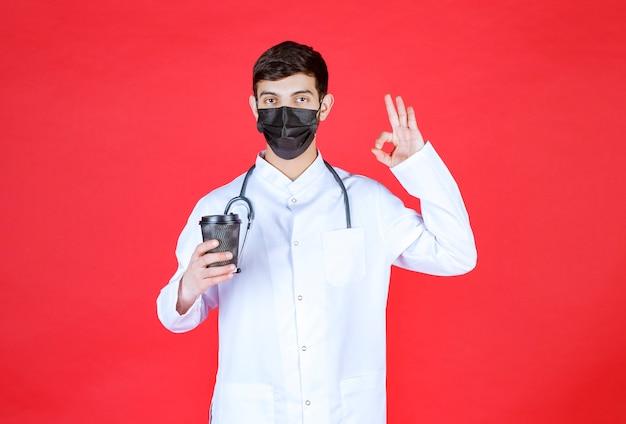 黒の持ち帰り用コーヒーカップを持って味を楽しんでいる黒いマスクの聴診器を持つ医者。