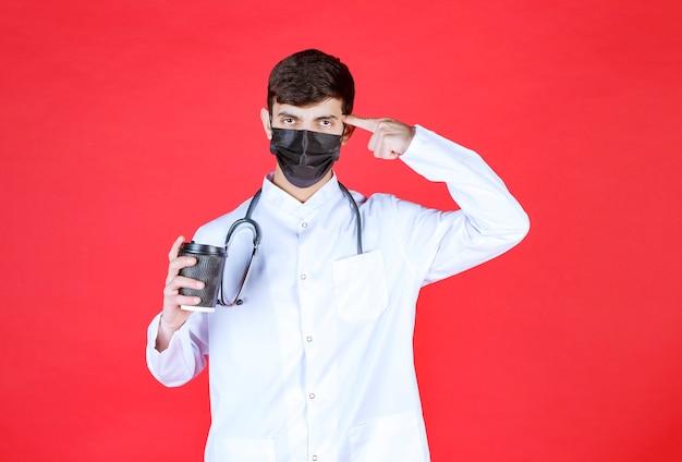 黒い持ち帰り用のコーヒーカップを持って考えている黒いマスクの聴診器を持つ医師。
