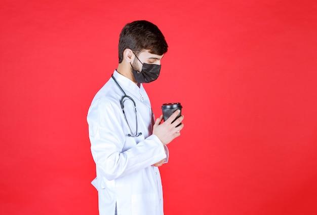 黒い持ち帰り用のコーヒーカップを持っている黒いマスクの聴診器を持つ医師。