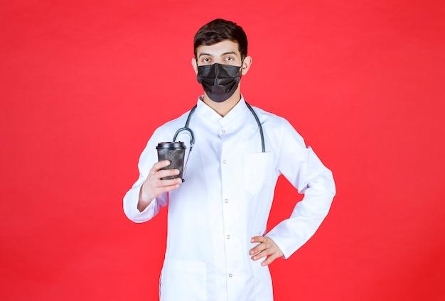 검은 테이크아웃 커피 컵을 들고 검은 마스크에 청진기를 가진 의사.