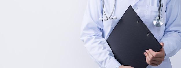 클립보드를 들고 흰색 코트에 청진기를 가진 의사, 흰색 배경에 고립 된 의료 기록 진단 작성, 닫기 보기를 잘립니다.
