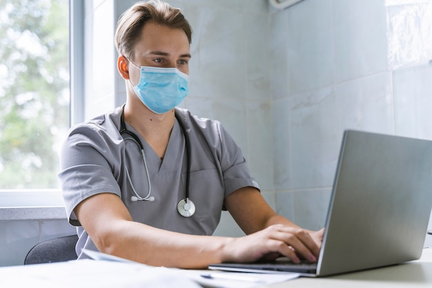Doctor with stethoscope and medical mask working on laptop