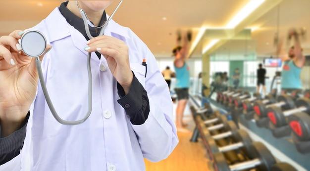 フィットネスルームの背景に聴診器を持つ医師スポーツ心臓病科学の概念