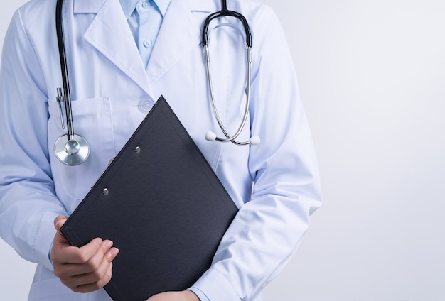 Doctor with stethoscope in white coat holding clipboard, writing medical record diagnosis, isolated on white background, close up, cropped view.