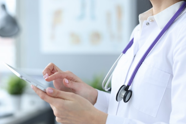 Doctor with stethoscope working on digital tablet closeup. online consultation concept