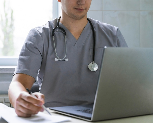 Doctor with stethoscope working on laptop
