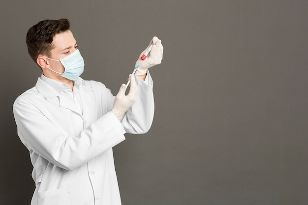 Doctor with surgical gloves and mask filling syringe with vaccine