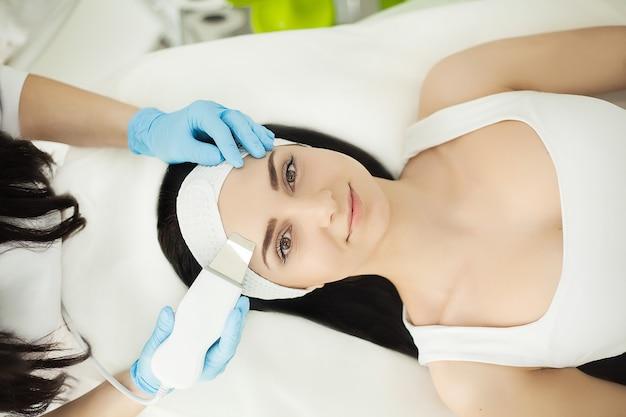 초음파 스크 레이버와 의사. 얼굴의 초음파 세척 절차를 수행합니다. 모델, 프로필. 미용 클리닉. 환자. 건강 관리, 클리닉, 미용.
