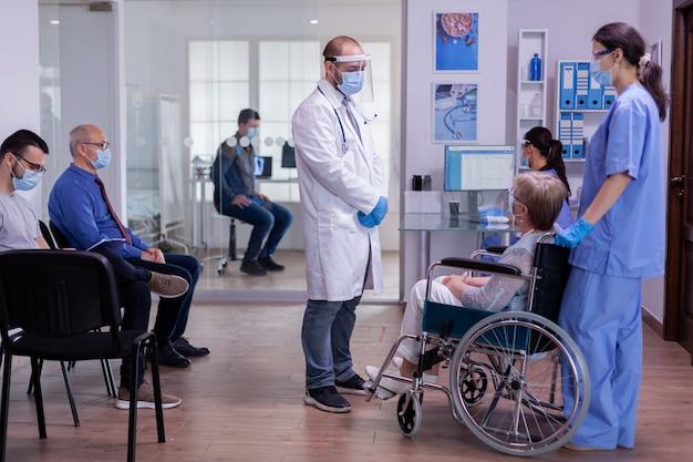 Врач с козырьком от коронавирусной инфекции обсуждает с парализованной пожилой женщиной в инвалидной коляске, стоящей в приемной больницы