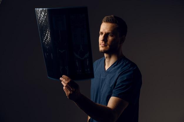 コロナウイルスcovid-19の病気の患者のx線スキャンを持つ医師。コンピュータ断層撮影。スキャンの写真を見ている医療ローブの外科医。健康診断のためのmri