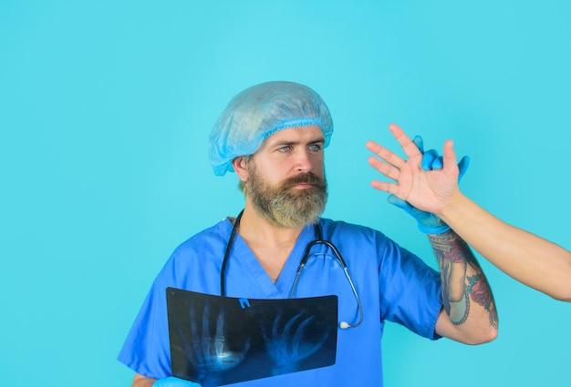 手のレントゲン写真のx線写真を持つ医者手のx線写真を持つ男性の医者医学博士x線
