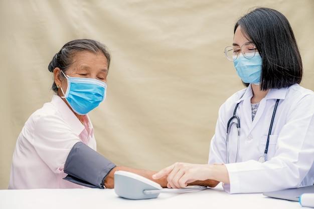 의사 여자는 혈압 모니터로 노인 환자를 평가하여 결과를 기록합니다