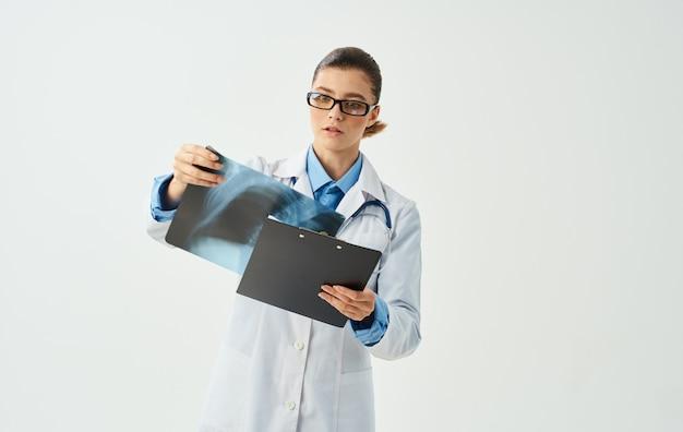 明るい背景のトリミングされたビューで胸部x線を調べる医師の女性。