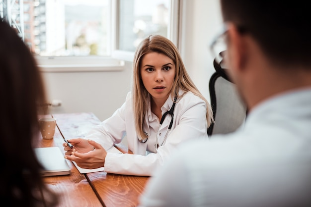 Doctor woman having conversation with young couple in office.