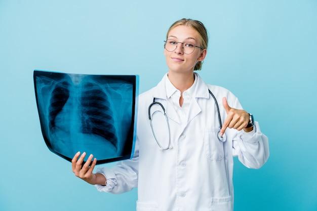 Женщина-врач держит сканирование костей на синих точках вниз пальцами