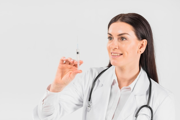 Doctor woman holding and looking at syringe