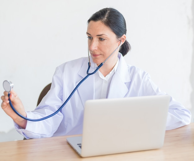 Doctor woman holding stethoscope in office and computer