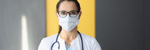 보호 의료 마스크와 흰색 코트에 의사 여자.