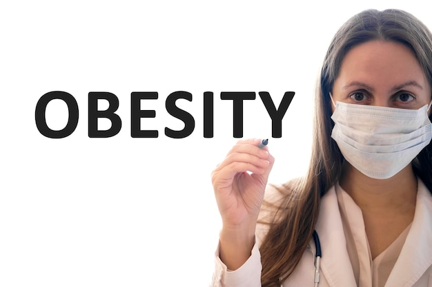 Doctor woman in a mask holds pen and writes obesity text