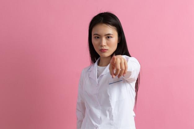 ピンクの背景に白い医療用ガウンで指のカメラを指している医者の女性。アジアの女性医療スタッフ。