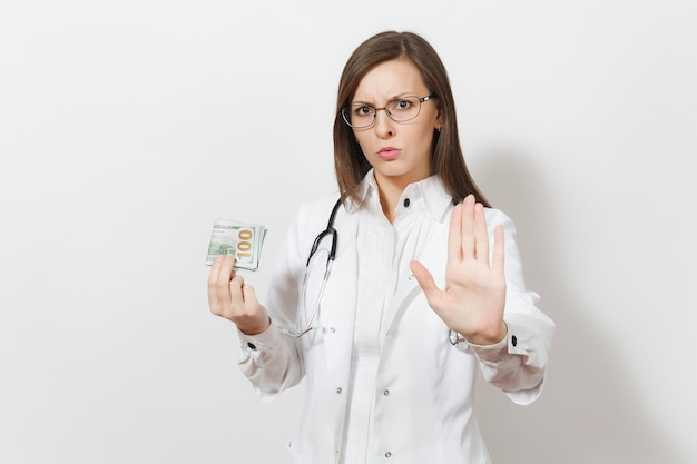 Doctor woman showing stop gesture with palm isolated on white background. female doctor in medical gown with stethoscope holding cash money banknotes, pack of dollars. healthcare personnel concept.