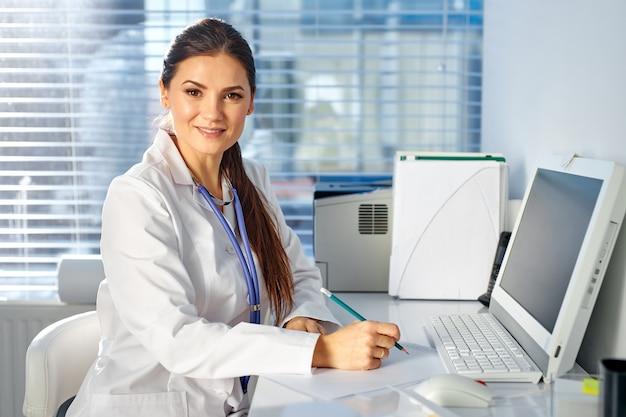 Женщина-врач, сидящая за столом, делая заметки, на рабочем месте, в медицинском костюме. профессиональный терапевт смотрит в камеру и улыбается