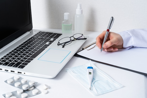病院のオフィスの職場でコンピューターを机に座って医師女性