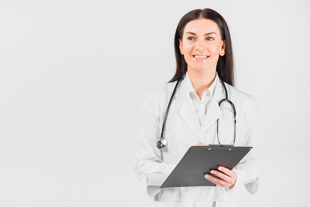 Doctor woman smiling, holding clipboard and looking away