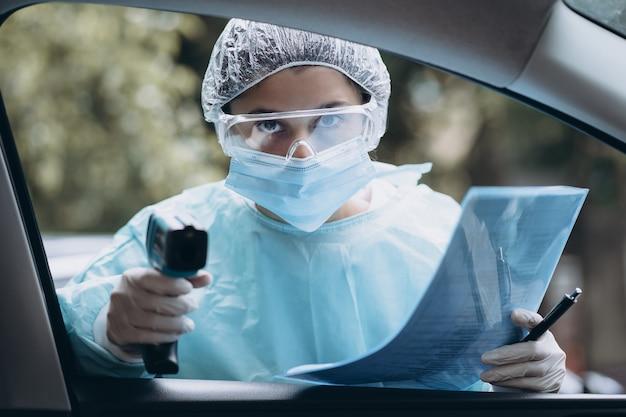 의사 여자는 적외선 이마 온도계 총을 사용하여 체온을 확인합니다.