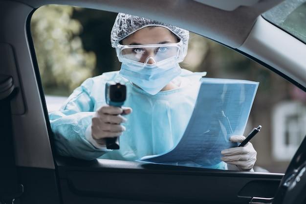Medico donna usa la pistola termometro a infrarossi per controllare la temperatura corporea