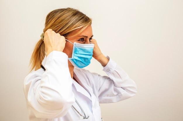 Доктор женщина носит маску. я работаю в больнице. белый фон