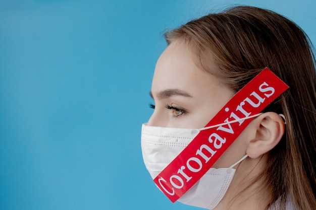 Doctor woman with surgical mask pointing to red paper with mesaage coronavirus on blue background. world health organization who introduced new official name for coronavirus disease named covid-19