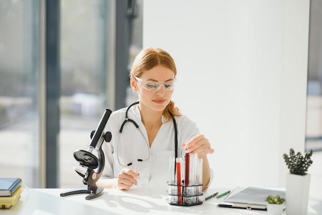 顕微鏡で働く医者の女性。研究室で顕微鏡を通して見ている女性科学者。顕微鏡で見ている学生、科学実験室の概念