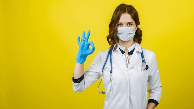 Женщина доктора womdoctor в маске и перчатках показывает хорошо знак на желтом фоне. баннер. свободный космонавт в маске и перчатках показывает знак