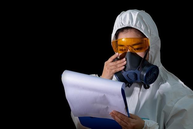 Врач-женщины держат папку с отчетами в белой химической защитной одежде и противогазовой маске