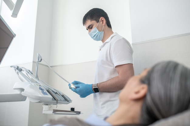 Doctor at work. male dentist in protective mask getting ready for teeth restoration