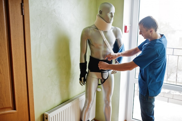 Doctor worker works with mannequin cast on arm and neck at prosthetist clinic.