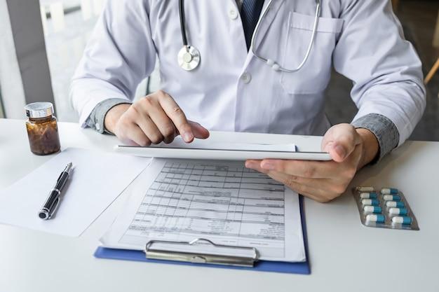 Доктор, работающий и использующий цифровую таблетку, отмечает информацию о бумажном отчете в больнице и медицинском стетоскопе, медицину в буфере обмена на столе.