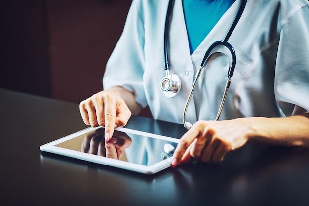 Doctor working on a digital tablet with copy space