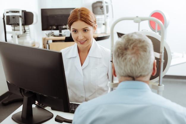 Врач усердно работает. рыжий молодой, но профессиональный глазной врач усердно работает при осмотре пациента