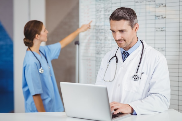 Doctor working on laptop with colleague pointing at chart