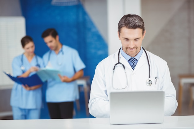 Doctor working on laptop with colleagues discussing