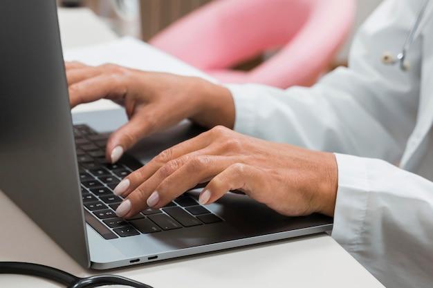 ノートパソコンのクローズアップに取り組んでいる医師