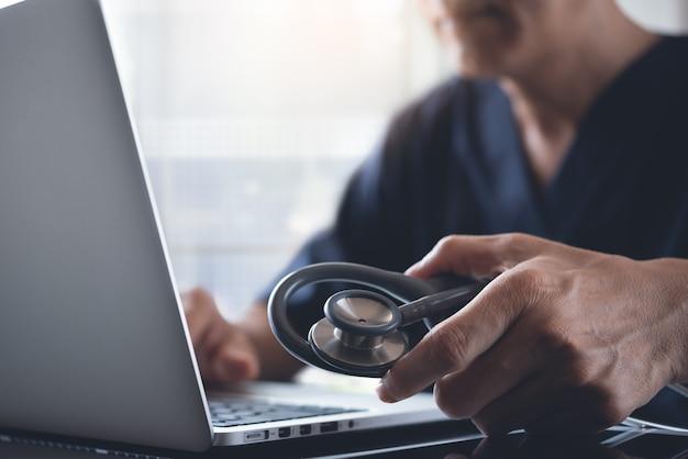 노트북 컴퓨터에서 작업하는 의사