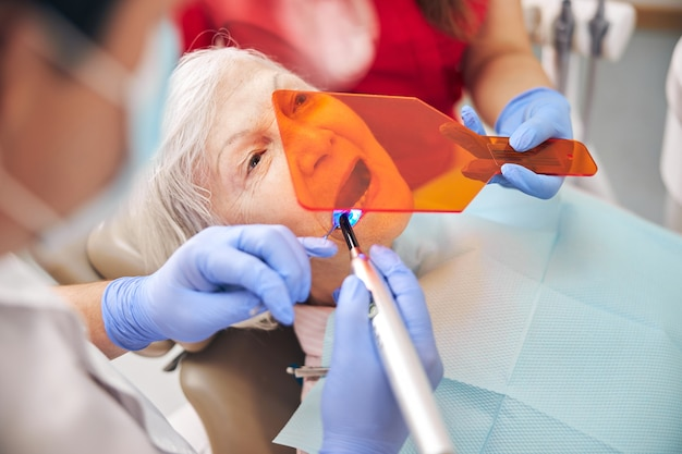 Doctor working with bonding composite filling material with ultraviolet light dental tool in modern clinic