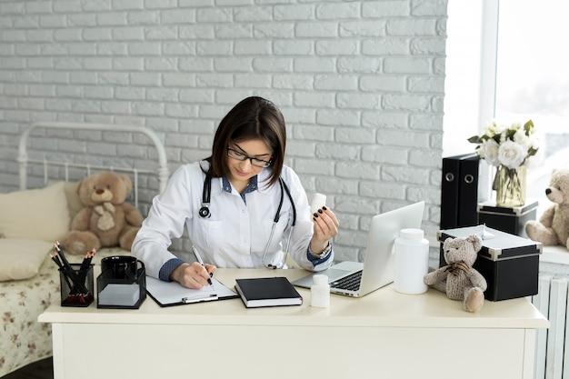 Доктор работает с ноутбуком и писать на документы.